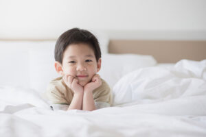 How to transition toddler from crib to bed. Cute Asian toddler lying on white bed.