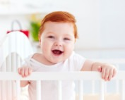 cute happy infant baby standing in a cot at home won't sleep