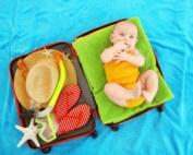 Cute baby and travel essentials in suitcase lying on blue bedspread