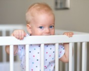Baby boy with blue eyes standing in crib not sleeping